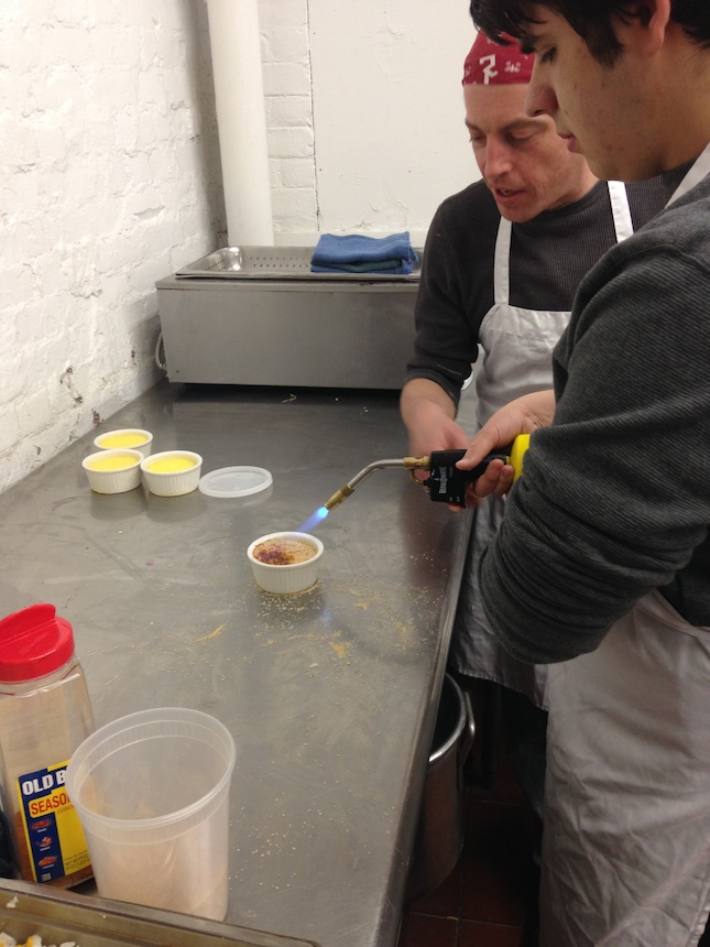 Chef-mentor Nate Wagner (left), of the Red Lion Inn demonstrates how to caramelize sugar on top of crème brûlée with a butane torch to Ryan Sherrick, participant in the Railroad Street Youth Project Culinary Arts Apprenticeship program; submitted photo.