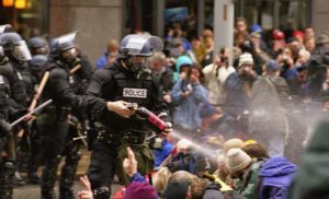 WTO protests in Seattle, November 30, 1999 Pepper spray is applied to the crowd; By Steve Kaiser from Seattle, US (WTO protests 10) [CC BY-SA 2.0 (https://creativecommons.org/licenses/by-sa/2.0)], via Wikimedia Commons.