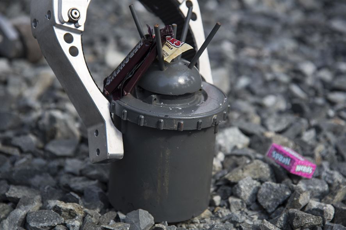 A landmine, also known as a 'bouncing betty,' sits with candy during a Range Day event at Misawa Air Base, Japan, Oct. 21, 2016. When set off by a trip wire, a first charge ignites at the bottom of the explosive causing it to bounce into the air, then a second charge causes the device to detonate; public domain photo by U.S. Air Force photo by Airman 1st Class Sadie Colbert.